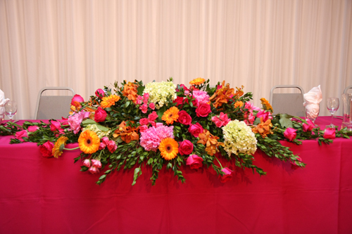 The altar arrangements contained pink peonies, Kiko roses, Twinkle Bride spray roses, green hydrangea, orange vanda orchids and Fabio gerberas, and were reused on the head table