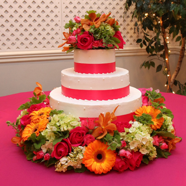 The cake was encircled Kiko roses, Twinkle Bride spray roses, green hydrangea, orange vanda orchids and Fabio gerberas