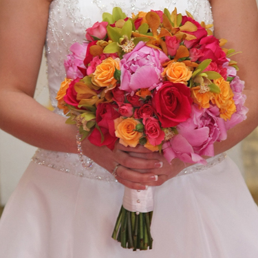 The bold bridal bouquet contained pink peonies, Kiko roses, Twinkle Bride spray roses, Macarena spray roses, green mini cymbidium orchids and orange vanda orchids