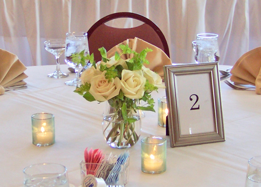 centerpiece with Green Fashion roses, bupleurum, and ribbon-wrapped votives