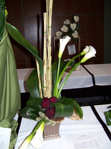 A sympathy arrangement with calla lilies, roses, aspidistra foliage, African reeds, sponge mushrooms, and reindeer moss.
