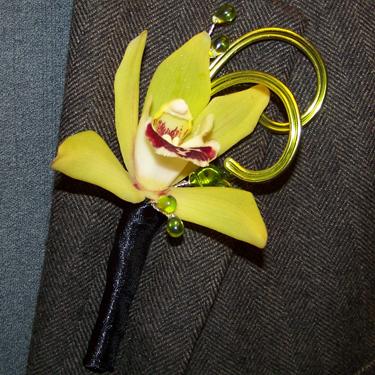Matching boutonniere with a single mini cymbidium, aluminum wire, and glass beads.