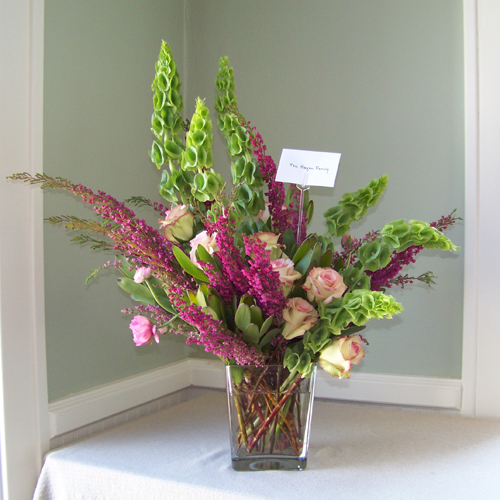 Sympathy arrangement with bells of Ireland, green leucadendron, Cezanne roses, pink ranunculus and heather