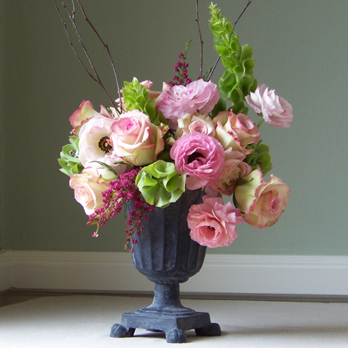 Romantic garden style arrangement with bells of Ireland, Cezanne roses, pink ranunculus, heather and birch branches in a cast iron urn.