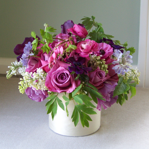 Silk wrapped cylinder vase with blue scabiosa, purple anemone, purple double tulips, Maritim roses, hot pink ranunculus, bleeding hearts, pink peonies and white lilacs