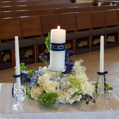 unity candle arrangement with delphinium, hydrangea, roses, stock and bells of Ireland