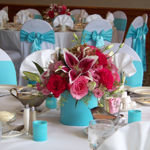 Low tiffany blue and pink centerpiece with Star Fighter oriental lilies, Hot Lady roses, Eliza roses, pink lisianthus, pink/green antique hydrangea and seeded eucalyptus