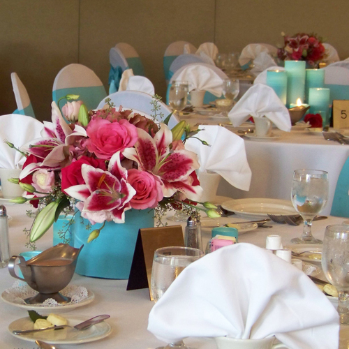 Low tiffany blue and pink centerpiece with a tiffany blue candle centerpiece in the background