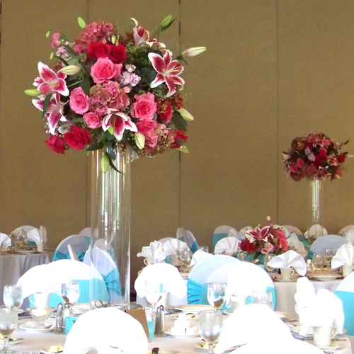 Tall centerpiece with Star Fighter oriental lilies, Hot Lady roses, Eliza roses, pink stock, pink lisianthus, pink/green antique hydrangea and seeded eucalyptus