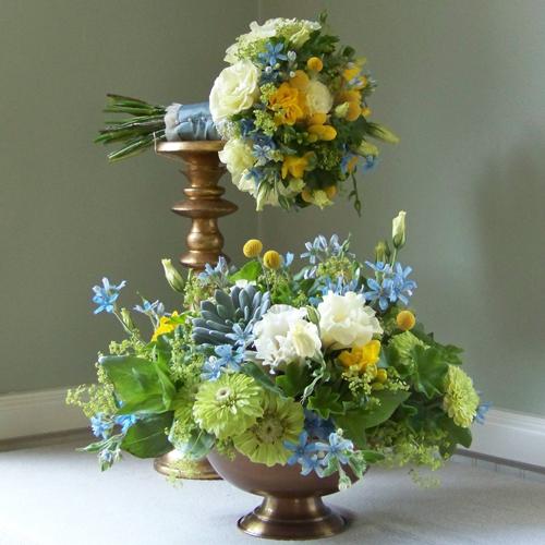 Bouquet and centerpiece containing tweedia, succulents, zinnias, alchemilla, geranium foliage, lisianthus, freesia and craspedia