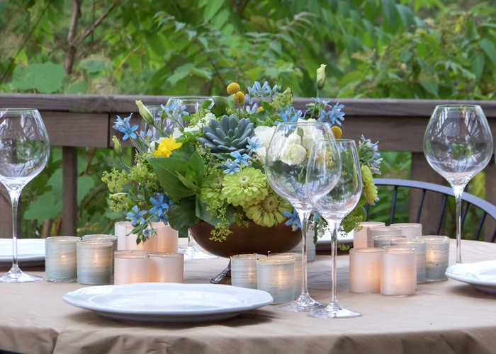 Romantic blue, green, yellow and ivory floral centerpiece in an antique gold urn, surrounded by silk-wrapped votives