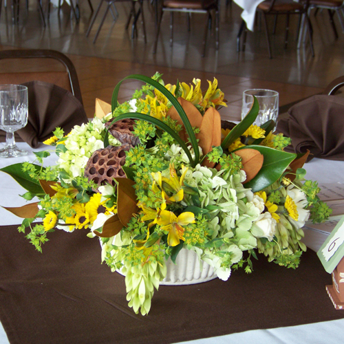 low centerpieces with dried lotus pods, hydrangea, magnolia foliage, tree of heaven, bupleurum, daisy poms, alstromeria, spray roses, and lily grass
