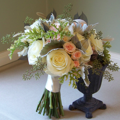 bridal bouquet containing black skeleton leaves, beige stripped coque feathers, Polar Star roses, Princess spray roses, Peach Vision spray roses, scented geranium, seeded eucalyptus, and dusty miller