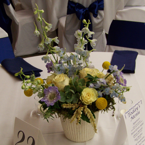 centerpiece containing scabiosa, delphinium, succulents, pieris, Cream Prophyta roses, and craspedia