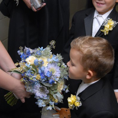 the ring bearer smelling the bridal bouquet