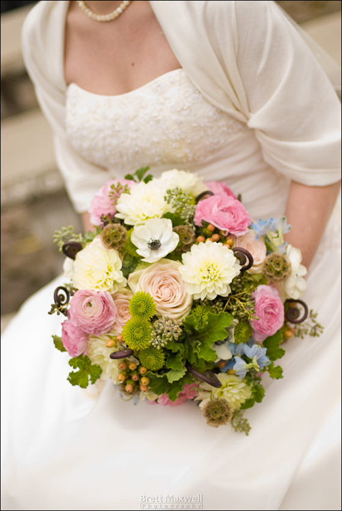 bridal bouquet with black privet berries, Uluhe fern curls, delphinium, black and white anemones, white dahlias, stellata pods, seeded eucalyptus, green hydrangea, Kermit button poms, scented geranium, Green Fashion roses, pink ranunculus, and Elite Amber hypericum.
