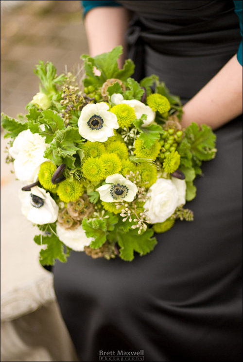 bridesmaid bouquet with black privet berries, Uluhe fern curls, black and white anemones, white ranunculus, stellata pods, seeded eucalyptus, green hydrangea, Kermit button poms, Green Condor hypericum berries, green wheat and scented geranium.