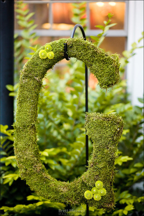 "Letter ""G"" monogram, covered in moss, and hung on a shepherd's hook"