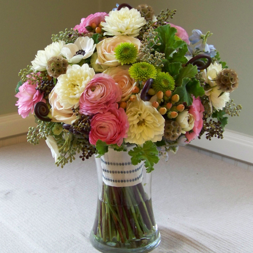 bridal bouquet with black privet berries, Uluhe fern curls, delphinium, black and white anemones, white dahlias, stellata pods, seeded eucalyptus, green hydrangea, Kermit button poms, scented geranium, Green Fashion roses, pink ranunculus, and Elite Amber hypericum