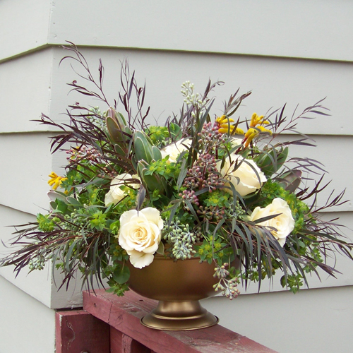 centerpiece with yellow kangaroo paws, Cream Prophyta roses, green leucadendron, agonis, bupleurum, and seeded eucalyptus in a gold footed bowl