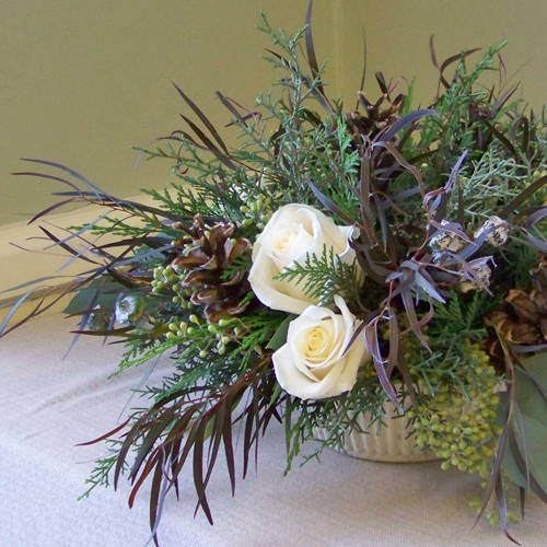 centerpiece with Vendela roses, seeded eucalyptus, Oregon cedar, Carolina sapphire, eucalyptus silver bells, agonis, and pine cones