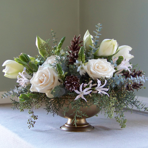 centerpiece with white amaryllis, Vendela roses, Star of Bethlehem, nerine lilies, leucadendron, seeded eucalyptus, Carolina sapphire, baby blue eucalyptus, and pine cones, in a gold footed bowl