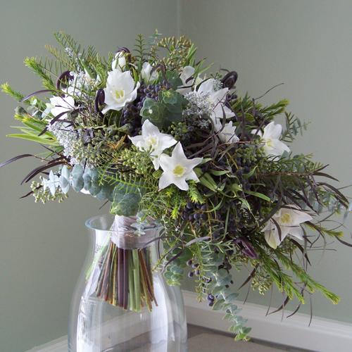 Cascade bouquet with Uluhe fern curls, agonis, privet berries, eucharis lilies, white sweet peas, green leucadendron, grevillea, honey bracelet, seeded eucalyptus, baby blue eucalyptus, silver bell eucalyptus, and kochia