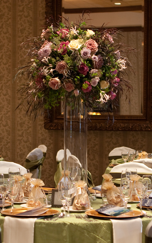 tall centerpiece with Amnesia roses, Maritim roses, Cream Prophyta roses, Little Silver spray roses, blush nerine lilies, agonis, bupleurum, and seeded eucalyptus on a 32 inch cylinder vase