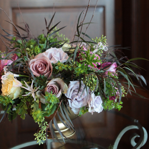 centerpieces with Amnesia roses, Maritim roses, Cream Prophyta roses, Little Silver spray roses, blush nerine lilies, agonis, bupleurum, seeded eucalyptus and birch branches in a gold footed bowl