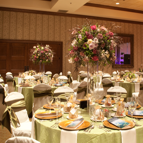 tall centerpieces with Amnesia roses, Maritim roses, Cream Prophyta roses, Little Silver spray roses, blush nerine lilies, agonis, bupleurum, and seeded eucalyptus on 32 inch cylinder vases