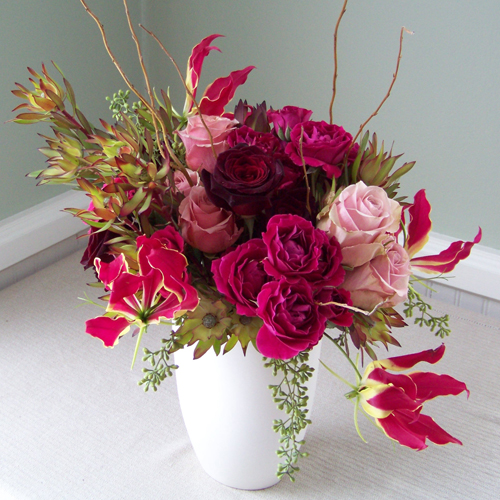 Valentine's Day arrangement with Black Baccara roses, Gloriosa lilies, Hot Majolika spray roses, Eos roses, leucadendron, seeded eucalyptus and curly willow