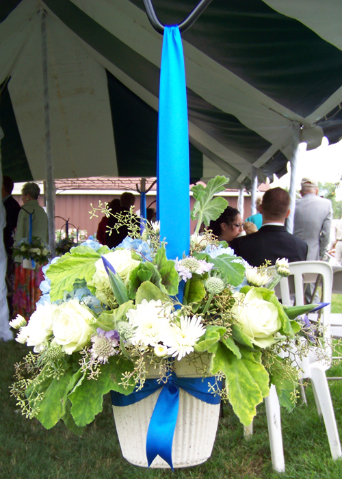 Aisle arrangement on shepard's hook doubles as centerpiece.  Contains iris, blue scabiosa, pale blue hydrangea, cushion poms, Green Tea roses, scented geranium and seeded eucalyptus.