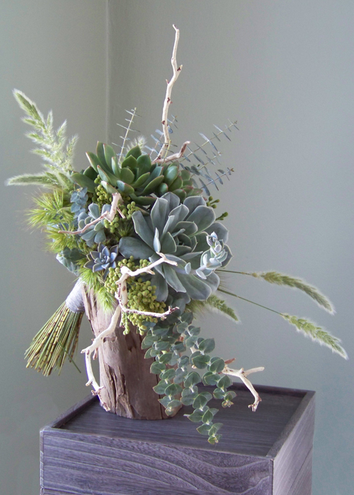 side view of bridal bouquet with manzanita branches, assorted succulents, berzelia, baby blue eucalyptus, bunny grass, and other assorted grasses wrapped with silver dupioni silk