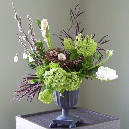 centerpiece, a nest of quail eggs is displayed in a small cast iron urn and is surrounded with French pussy willow, hyacinth, agonis, viburnum, ranunculus, euonymus foliage, jade trachelium and snow drops