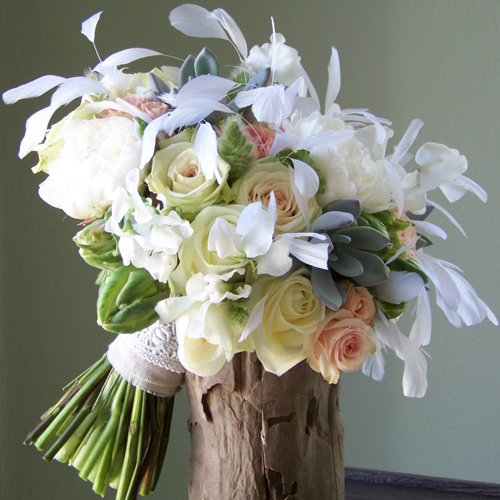 bridal bouquet with white sweetpeas, Polar Star roses, white peonies, white French tulips, green parrot tulips, bunny tail grass, succulents, scented geranium, Green Fashion roses, Star Blush spray roses, a linen and ivory lace stem wrap, and white eyelash feathers