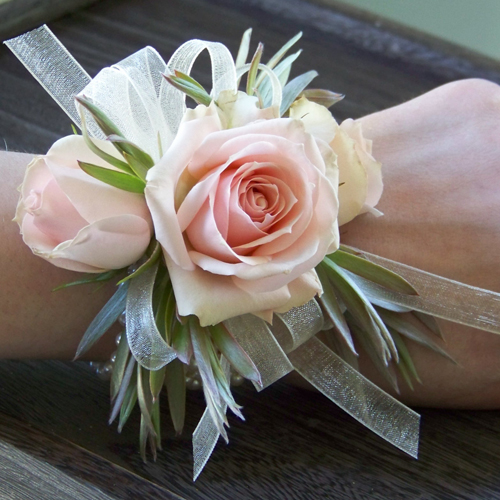 corsage with Star Blush spray roses, green leucadendron and ivory chiffon ribbon on an ivory pearl bracelet