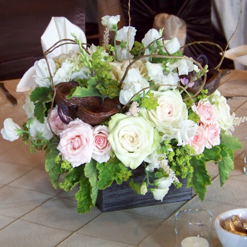 centerpiece with white sweet peas, white hydrangea, Green Fashion roses, blush astilbe, Star Blush spray roses, ixia, alchemilla, bupleurum, scented geranium, curly willow, badam nuts and fern curls in a Kiri wood box
