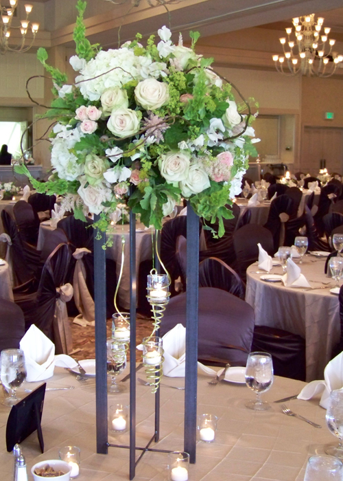 tall centerpiece with white sweet peas, white hydrangea, Green Fashion roses, blush astilbe, Star Blush spray roses, alchemilla, bupleurum, bells of Ireland, scented geranium, and curly willow.  An iron stand and spiraled hanging votive holders complete the look.