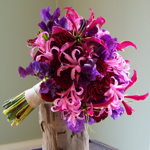 hand-tied bouquet with Hearts roses, Rubicon spray roses, gloriosa lilies, nerine lilies, and sweet peas