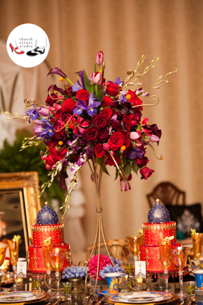 Moulin Rouge themed centerpiece with dendrobium orchids, Schwartzwalder mini callas, Black Baccara roses, Freedom roses, gloriosa lilies, Hot Majolika spray roses, tulips, craspedia, iris, muscari and gold fern curls.