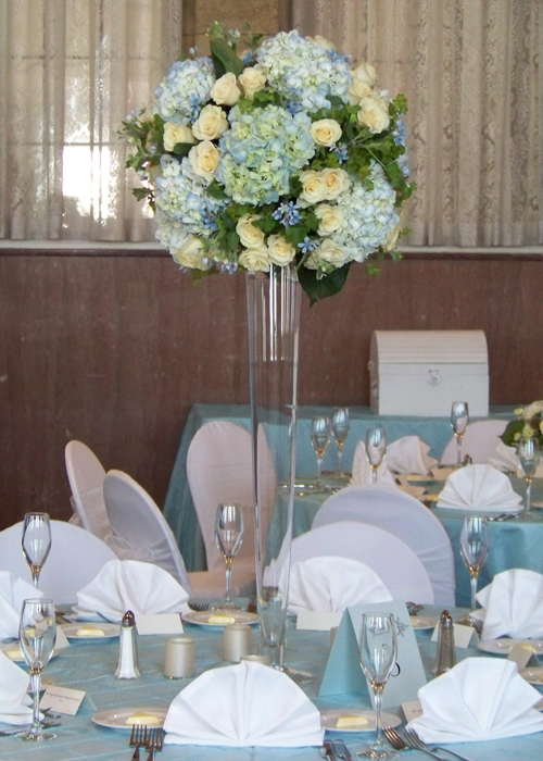 "Tall centerpiece with tweedia, pale blue hydrangea, Cream Prophyta roses, bupleurum, and geranium in a 32"" pilsner vase"