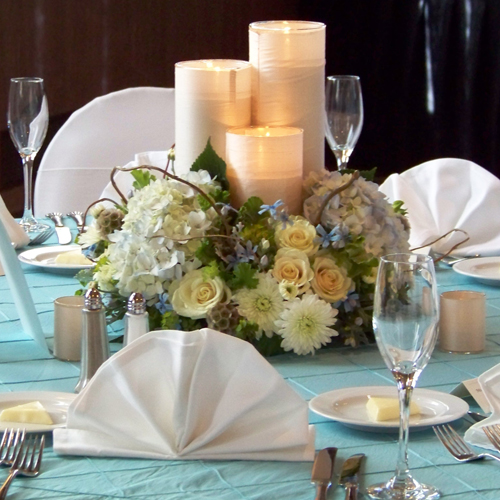 Centerpiece with a trio ivory silk wrapped candles surrounded by a ring of tweedia, pale blue hydrangea, Cream Prophyta roses, Polaris cushion poms, bupleurum, geranium, scabiosa pods, and curly willow branches