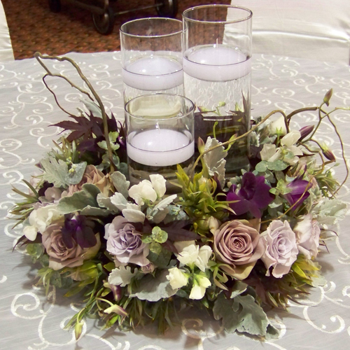 centerpiece with a trio floating candles surrounded by a ring of curly willow, white sweet peas, little silver spray roses, amnesia roses, dendrobium orchids, Japanese maple, green leucadendron, baby blue eucalyptus and dusty miller