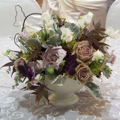 low centerpiece with curly willow, white sweet peas, little silver spray roses, amnesia roses, dendrobium orchids, Japanese maple, green leucadendron, baby blue eucalyptus and dusty miller in an ivory footed bowl
