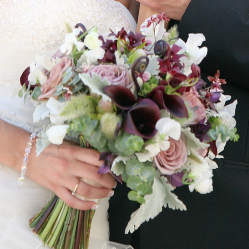 bridal bouquet containing white sweet peas, amnesia roses, Schwartzwalder mini callas, Burana Sindy dendrobium orchids, fern curls, Sharry Baby oncidium orchids, scented geranium, green leucadendron, bunny grass, baby blue eucalyptus and dusty miller