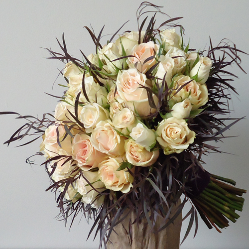 hand tied bouquet with High & Arena roses, Porcelina spray roses, and agonis
