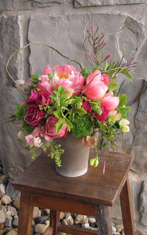 Centerpiece with curly willow branches, jasmine vine, David Austin Darcey garden roses, Hot Majolika spray roses, Coral Charm peonies, Romantic Antike garden roses, peach sweet peas, alchemilla, Green Trick dianthus, scented geranium and Jade trachelium