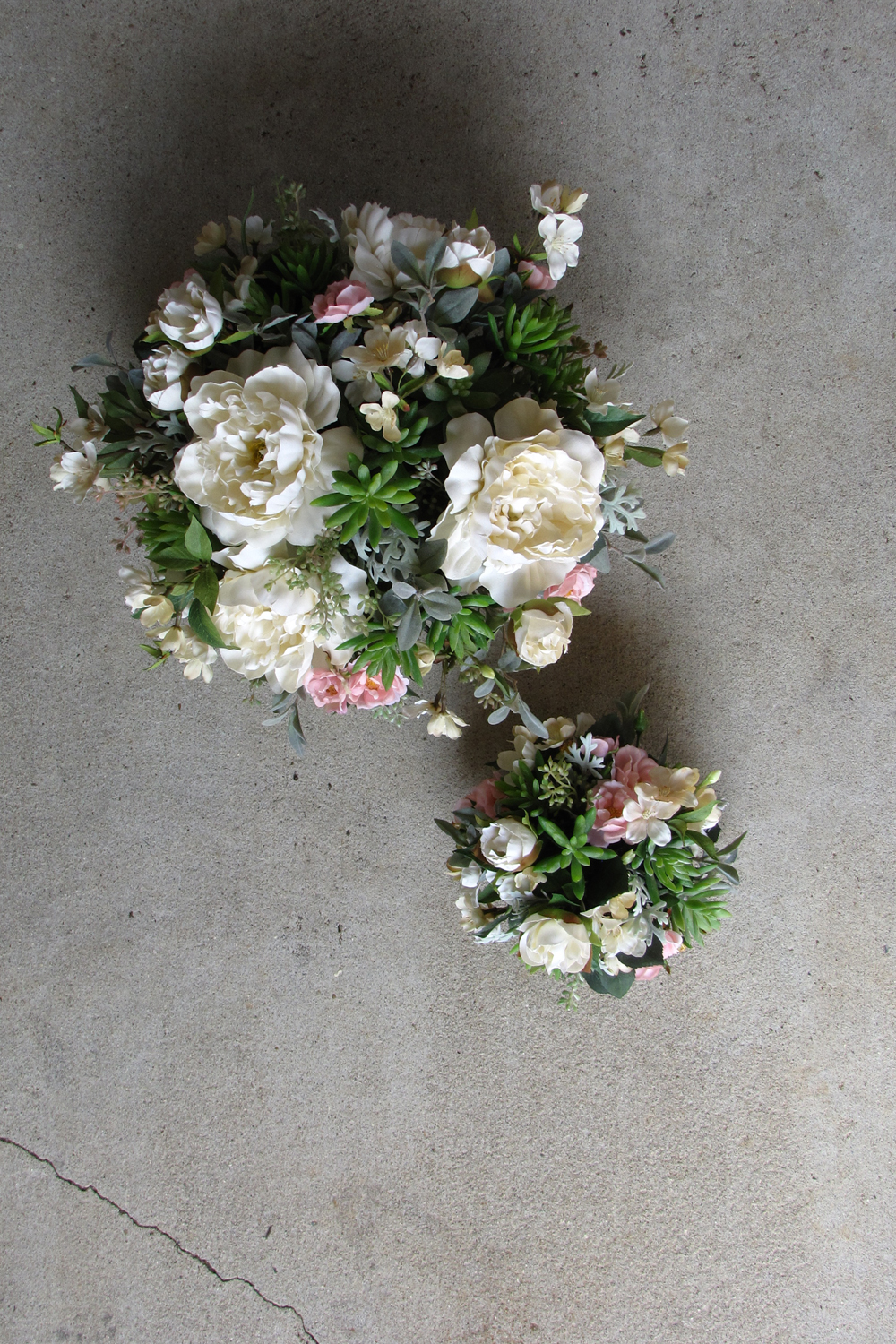 overhead view of centerpieces with blush spray roses, ivory peonies, ivory cherry blossoms, succulents, seeded eucalyptus, myrtle, and dusty miller