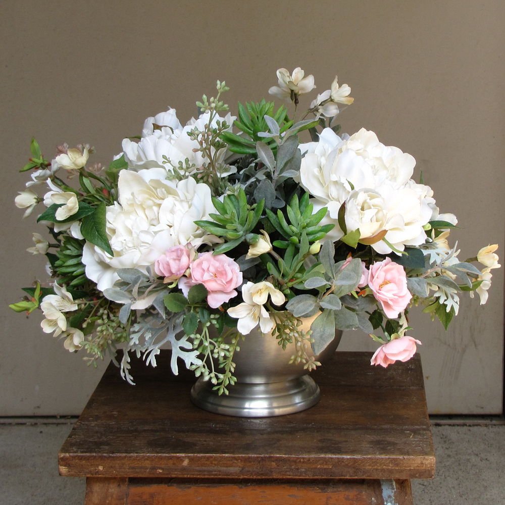 centerpiece with blush spray roses, ivory peonies, ivory cherry blossoms, succulents, seeded eucalyptus, myrtle, and dusty miller in a Revere bowl