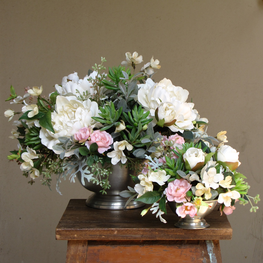 silk centerpieces with blush spray roses, ivory peonies, ivory cherry blossoms, succulents, seeded eucalyptus, myrtle, and dusty miller in Revere bowls